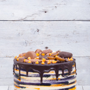 Bright fresh homemade cake decorated with candies, dark and orange chocolate on a white wooden background